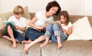 Mom and two kids on the couch looking at papers